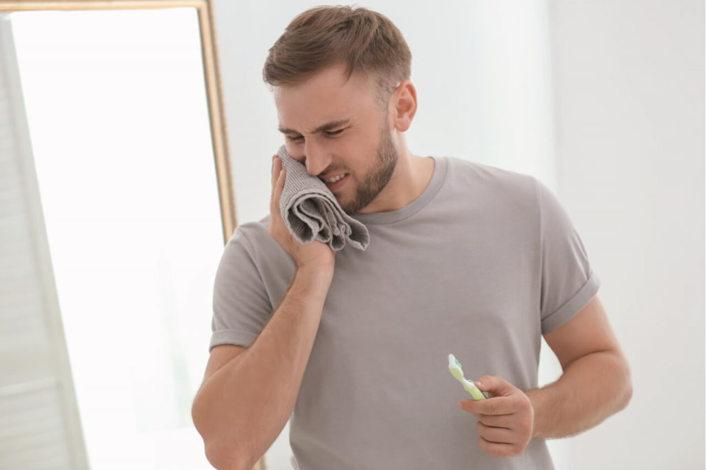 man experiences tooth sensitivity after brushing